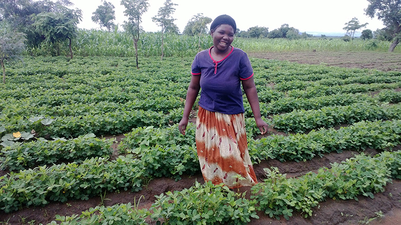 Beneficiary in Malawi stands next to crops