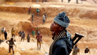 A soldier from the Congolese Rebel Army FPC watches artisanal miners at work in Musia Gold Mine in the Democratic Republic of Congo, North Kivu Province. Photo: James Oatway / Panos Pictures.