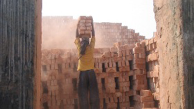 A construction worker carrying bricks at a brick making factory