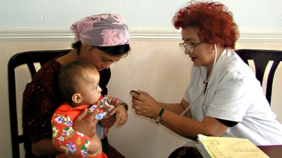 A health worker performs a check up on a baby as his mother holds him.