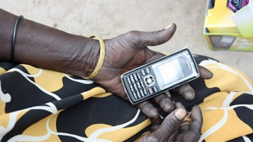 Woman in Sudan learns about mobile phone surveys.