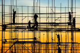Construction site, silhouettes of construction industry workers on scaffolding against the sunset light. Photo: Igor Stevanovic