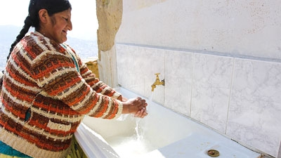 A woman washes her hands in La Paz
