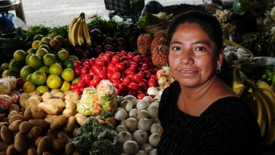 A woman tends to her produce post in a market in Guatemala City, Guatemala.