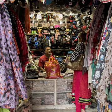 A woman purchases clothes from a store in Lalitpur, Nepal.
