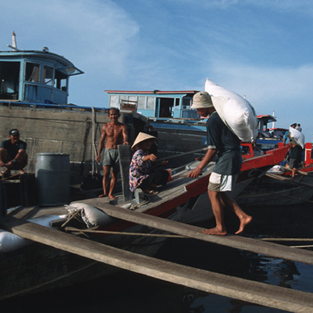 Workers load sacks onto a boat moored on the banks of the Saigon river. Photo: © Tran Thi Hoa / World Bank