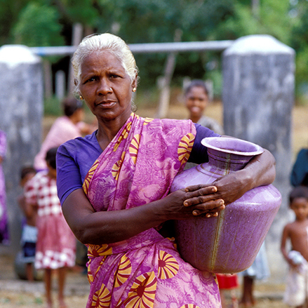 Woman with water container at well. Sri Lanka.