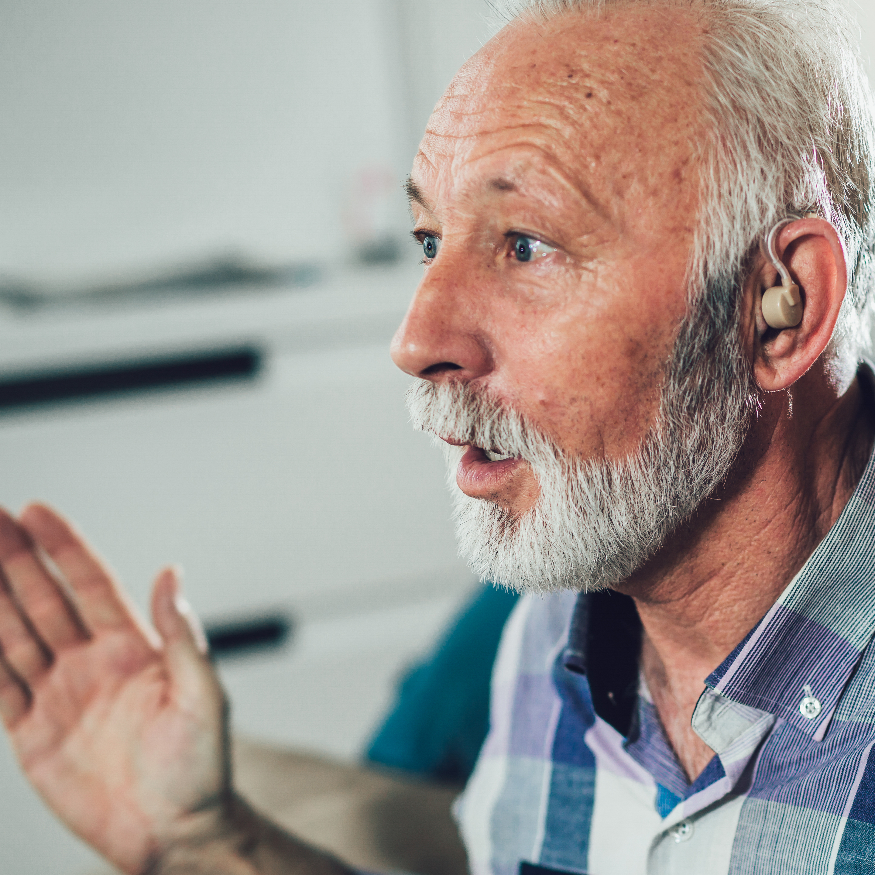 A man looks surprised at the difference a hearing aid can make.