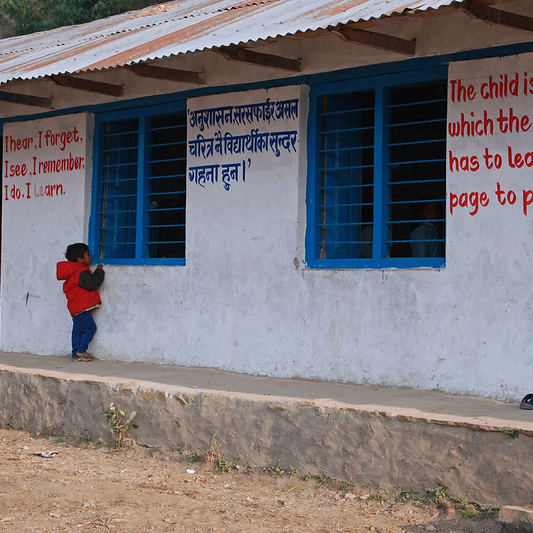 A young boy peeking through the window of an empty classroom in Nepal. Photo: © Simone D. McCourtie/World Bank