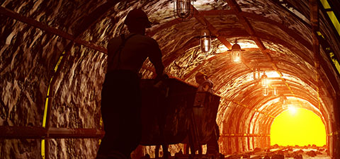 Workers pushing the cart in the mine. © iurii/Shutterstock