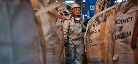 A woman employed by a copper and gold mine in Mongolia walks past bags ready for shipment. © Khasar Sandag/IFC