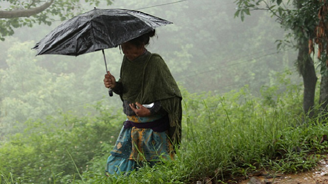 A woman walks under an umbrella in rural Nepal. Photo © Aisha Faquir/World Bank