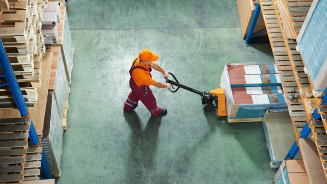 Worker with fork pallet truck stacker in warehouse loading furniture panels. Photo: Shutterstock/Dmitry Kalinovsky