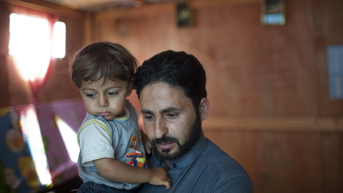 Ahmad holds his son Mouath in their makeshift home in the Ketermaya refugee camp; Photo © Dominic Chavez