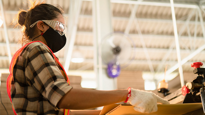 Woman worker wearing face mask during working in factory. Copyright: Chatchai.wa/Shutterstock