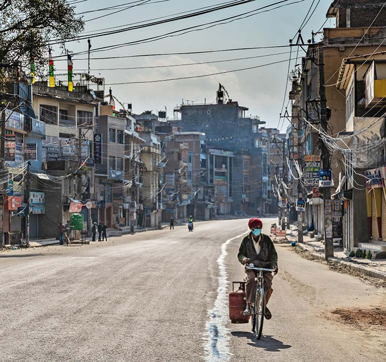 A man delivers household gas on a bicycle on an empty street in Kathmandu, Nepal, in March 2020. Photo: © Denis Dymov/Shutterstock