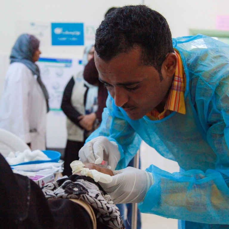 A doctor applying IV fluid to a woman who is suffering from suspected cholera in Aden, Yemen - Mutaz Fuad  | World Bank