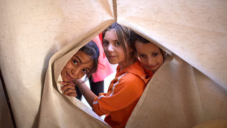 Syrian refugee children look through a sheet at the Nour Beach House in Chekka, Lebanon - © UNHCR/Shawn Baldwin