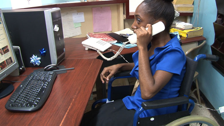 Kavian Moran answers phones at the YMCA in Kingston, Jamaica