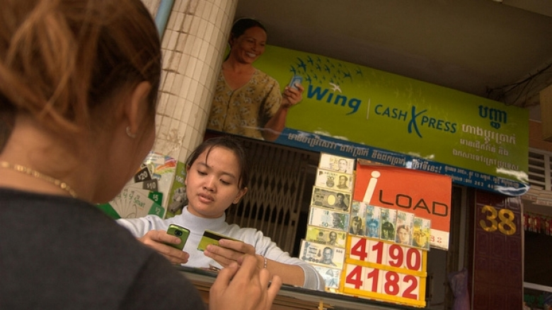 Two women conduct a financial transaction with a mobile phone and card © World Bank