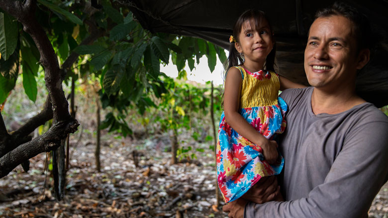 Yamid Duran Ramirez holds his daughter Leyla Duran Vergora after working on his farm where he grows passion fruit, in the township of La Paz, Colombia on January 12, 2015. Photo © Dominic Chavez/World Bank