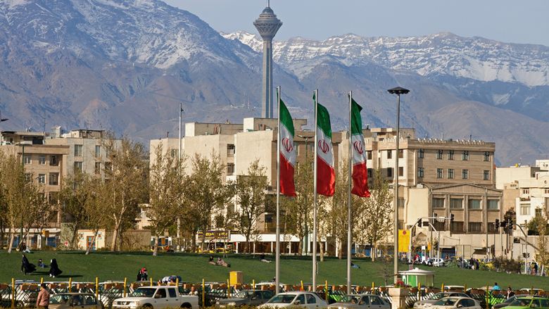 Alborz Mountains, in the city of Tehran, appear behind three Iranian flags.