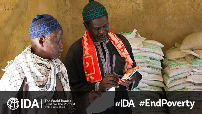 Two men in Senegal talk as one uses a calculator. Behind them, agricultural bags are stacked. IDA logo and End Poverty words are on the image © International Development Association