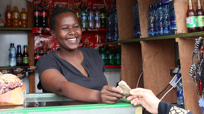 Woman shop owner in Mombasa, Kenya receives cash payment from a customer