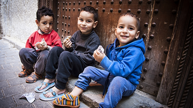 Group of small kids sitting on a step after playing in the streets of Asilah - La bionda sulla Honda | Shutterstock.com