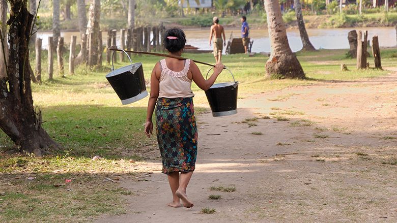 A woman carrying water in Laos.