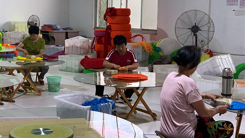 Three people sit at tables weaving in a Taobao village in China