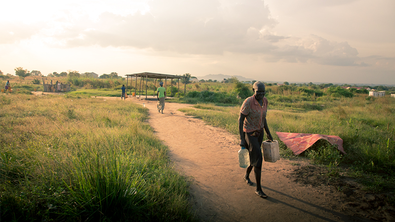 A man carries containers in South Sudan