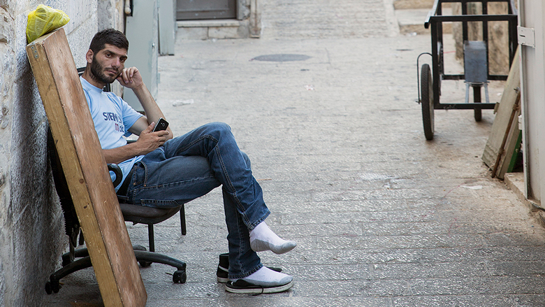 A man holds his phone while sat on a chair.
