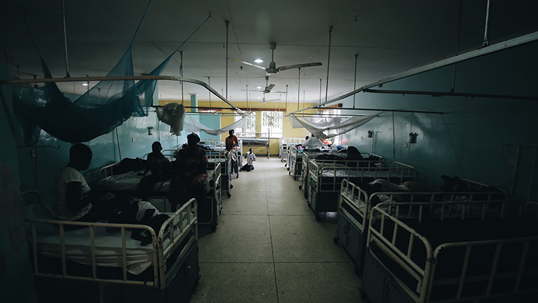 African people with their children sitting on the beds in little hospital in Africa, talking.