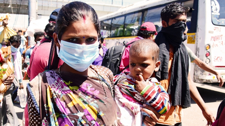 Migrant woman with a baby wearing a mask as a preventive measure at Delhi's Anand vihar bus terminal during the nationwide lock down. Photo: rajput/SOPA Images/Shutterstock