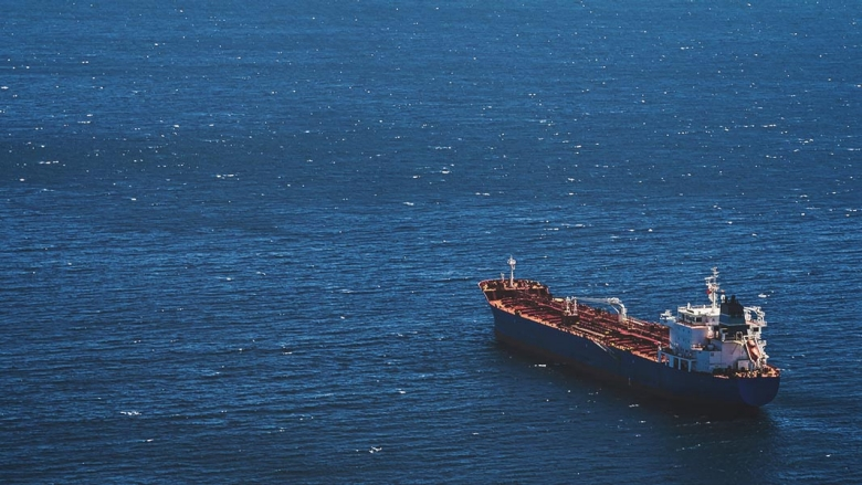 An empty cargo ship sails alone in the sea. © sergeisimonov/Shutterstock