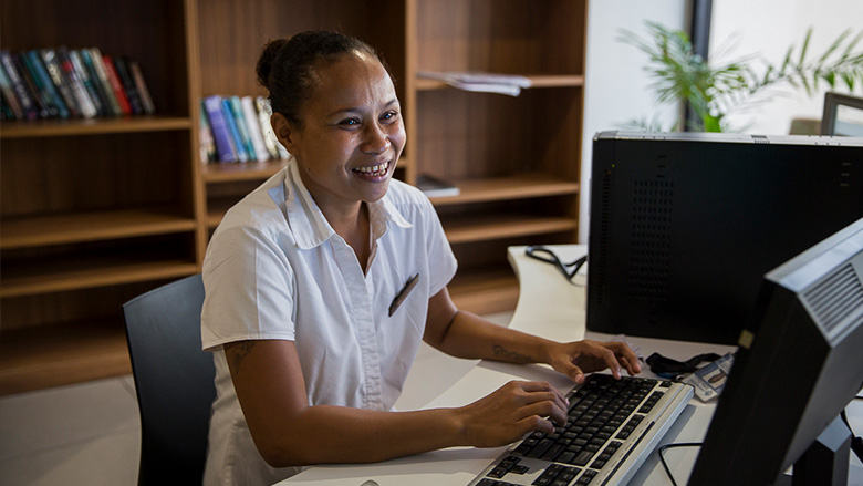 A woman that is employed at a hotel in Papua New Guinea smiles while sitting at her computer