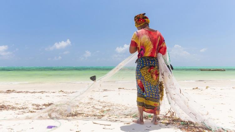 A woman fishing on Paje beach, Zanzibar, Tanzania. Photo: © Matej Kastelic/Shutterstock