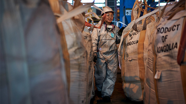 A woman employed by a copper and gold mine in Mongolia walks past bags ready for shipment