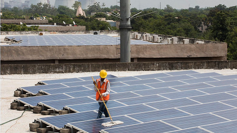 worker cleans solar panels on the rooftop of a building in Gandhinagar, India