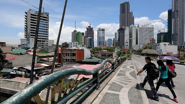 Pedestrians cross over the Pasig River in the City of Makati, Philippines