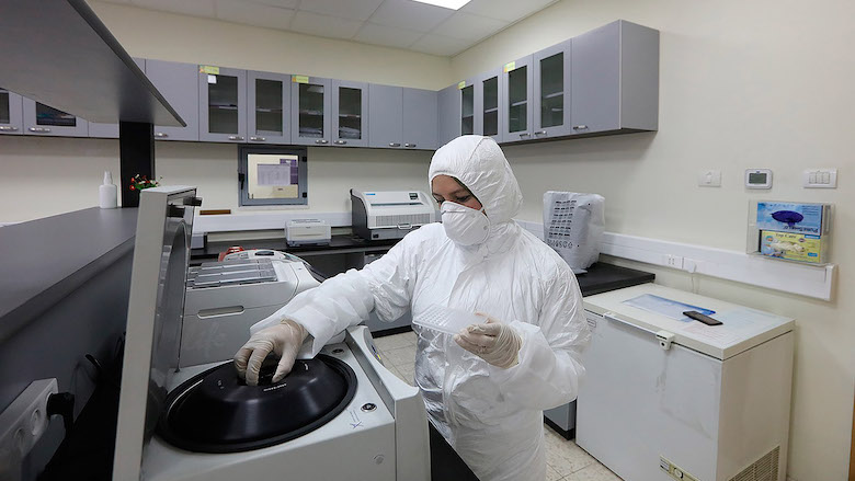 A female laboratory technician works on COVID-19 tests at the Central Public Health Laboratory in Ramallah City.