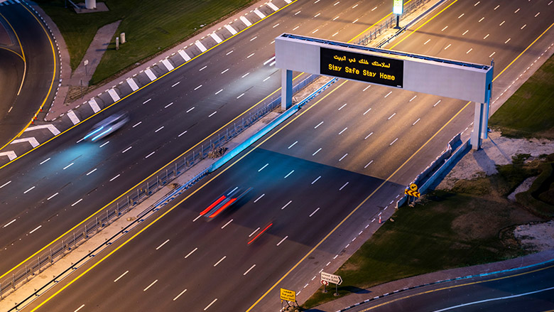 Empty highway in Dubai because on coronavirus. Sign advertising the Stay Home Stay Safe campaign.