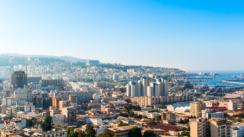 A landscape of Algiers city from Maqam Echahid monument, Algeria, appears in the distance.