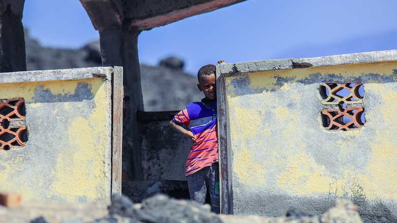A child stands near a traditional house in Tadjoura, Djibouti.