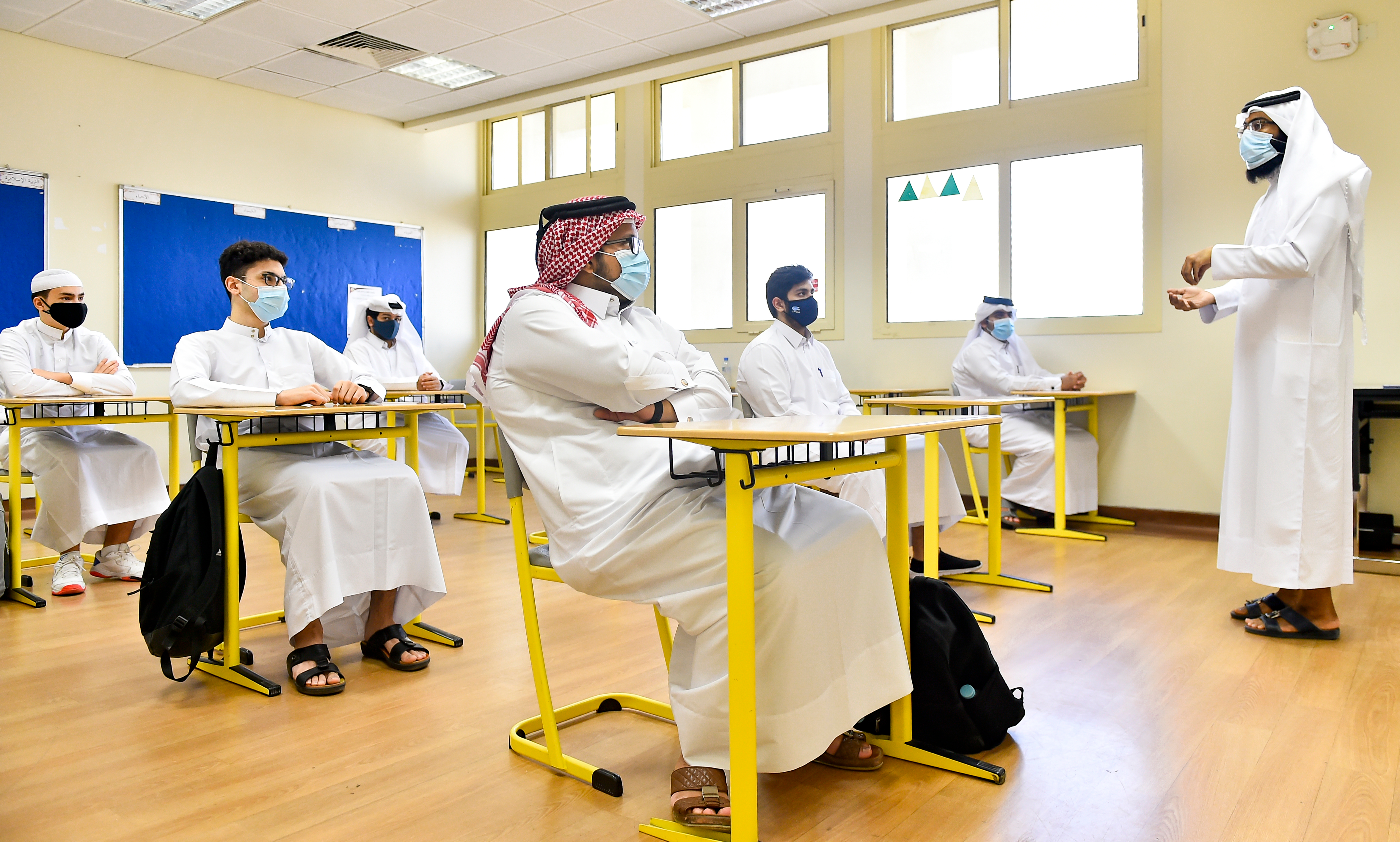 Students wear face masks and maintain social distance in a classroom on the first day of school at a Secondary School in Doha, Qatar.