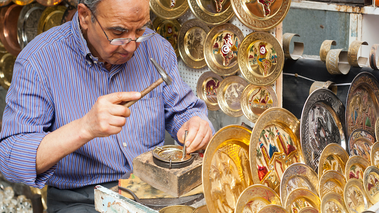 A craftsman punches out a pattern on a decorative brass plate at the souq market in Tunis, Tunisia.