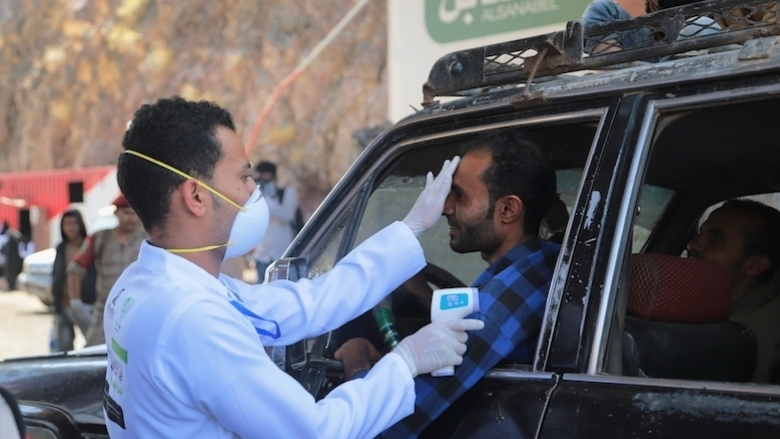 A doctor measures the temperature of a driver in the city of Taiz, Yemen.