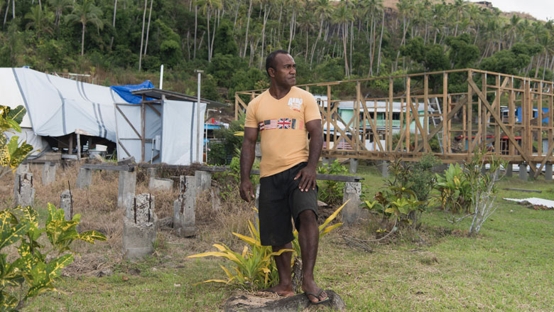 Rai Tabusoro stands at the site of his former home, current home and future home in Nabukadra, a coastal village in Ra Province, Fiji. Ra Province was one of the hardest hit by Cyclone Winston in 2016. Photo: Alana Holmberg/World Bank
