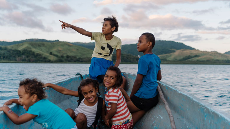Children from VuniSaviSavi, Fiji, sit in the village boat as they travel to their favorite swimming spot, a deep hole in the coral reef called 'The Tomb', not far from shore. Photo: Alana Holmberg/World Bank